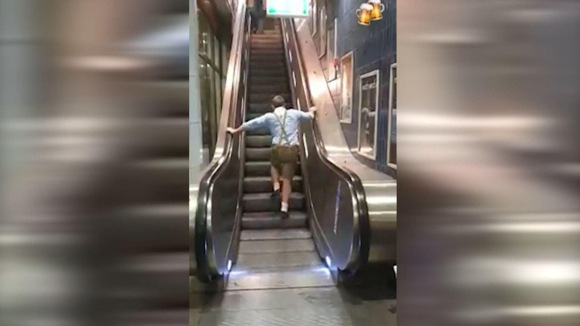Dickschädliger Wiesnbesucher kämpft mit der Rolltreppe