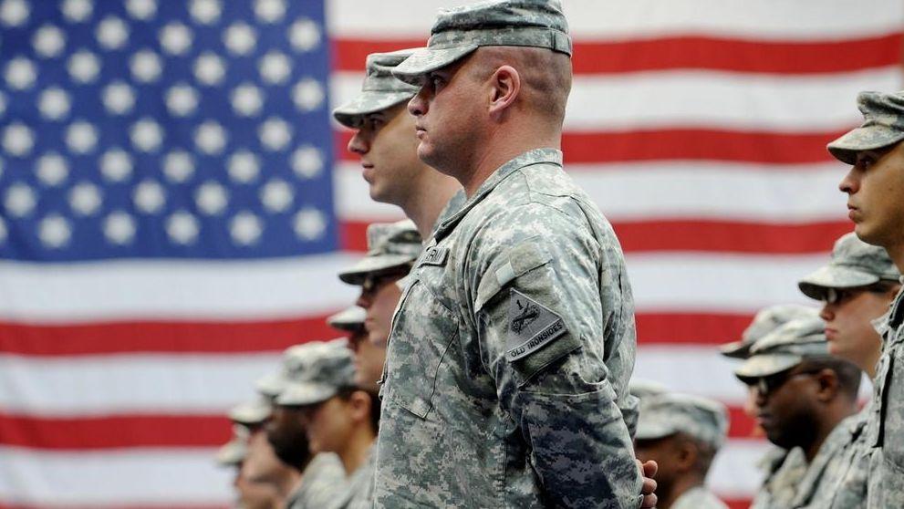 US-Soldaten stehen nach ihrer Ankunft auf der US-Airbase in Wiesbaden-Erbenheim vor einer US-Flagge.