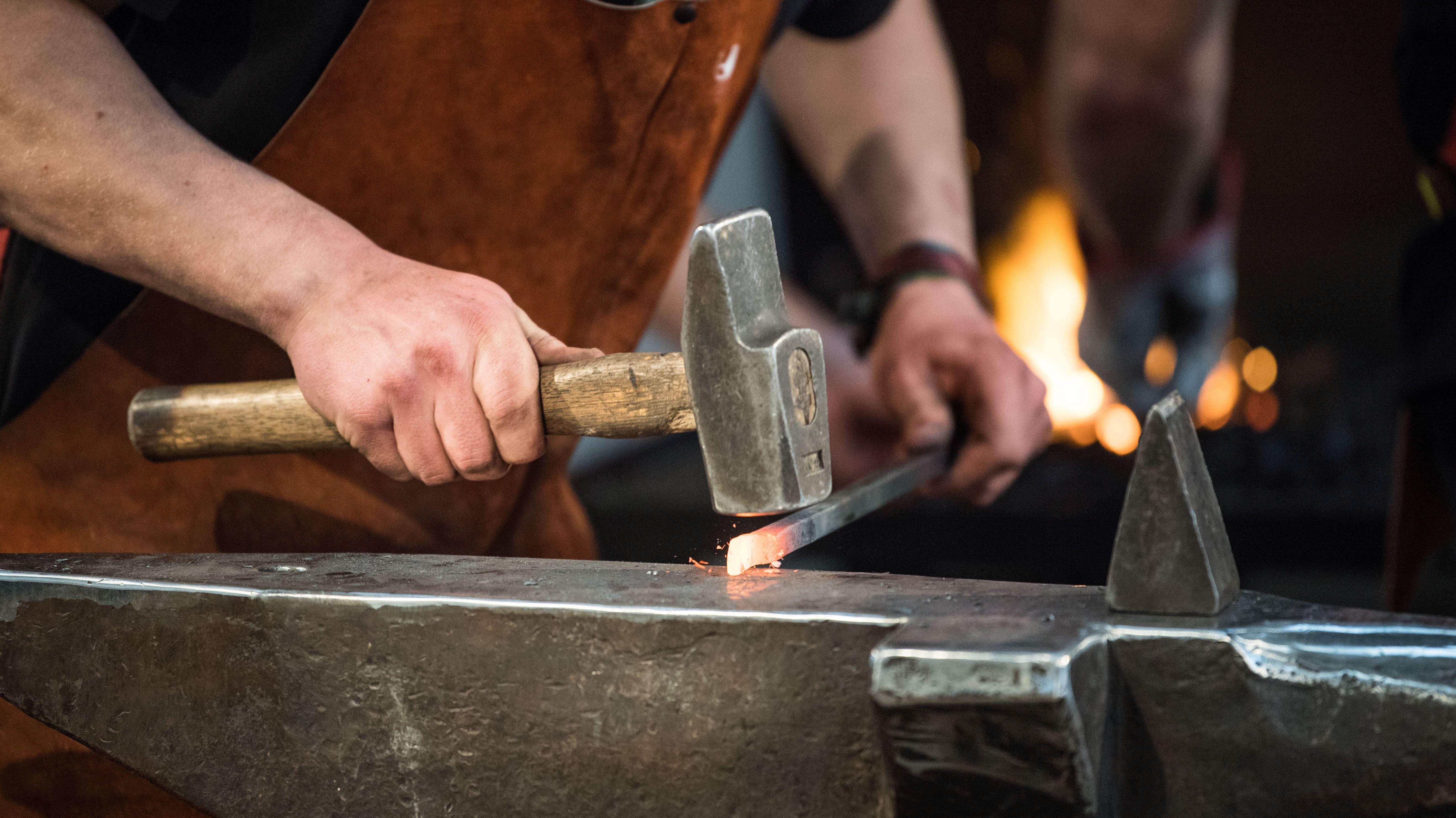 Ein Schmied bearbeitet ein Stück Eisen