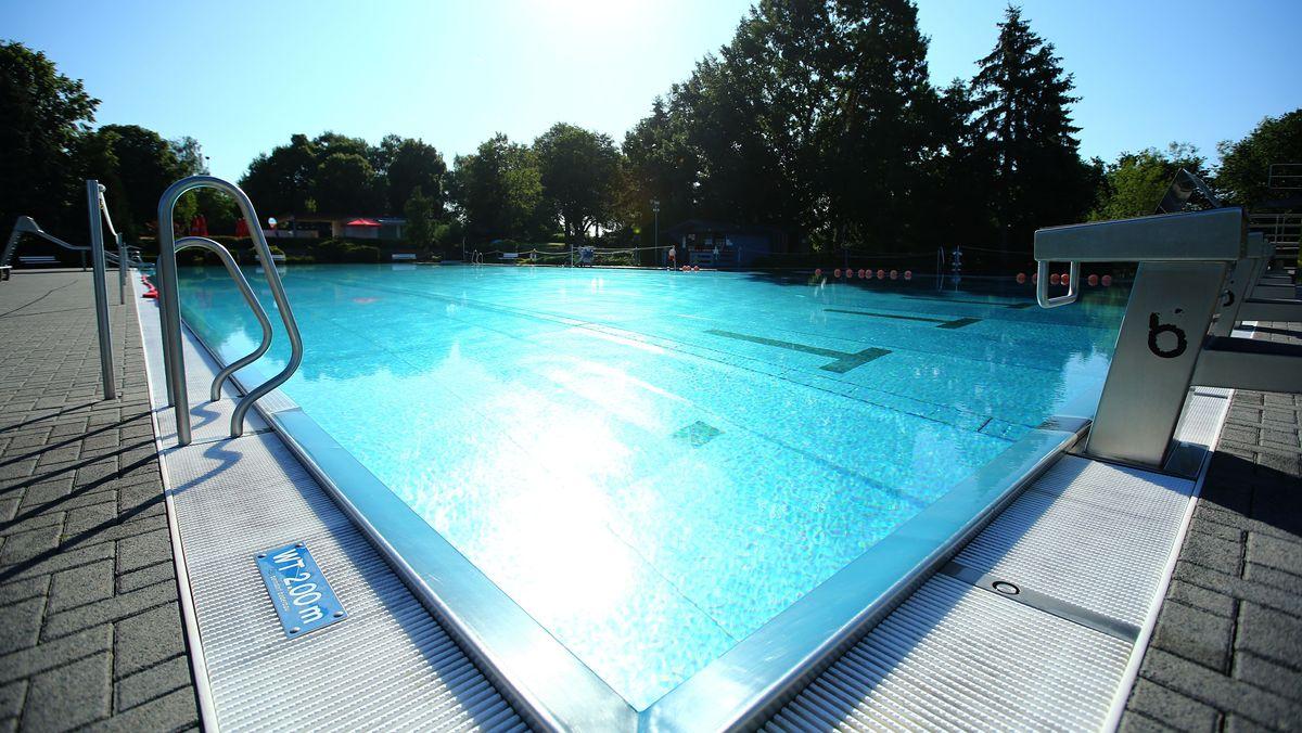 Symbolbild: Leeres Schwimmbecken eines Freibades im Sonnenschein.