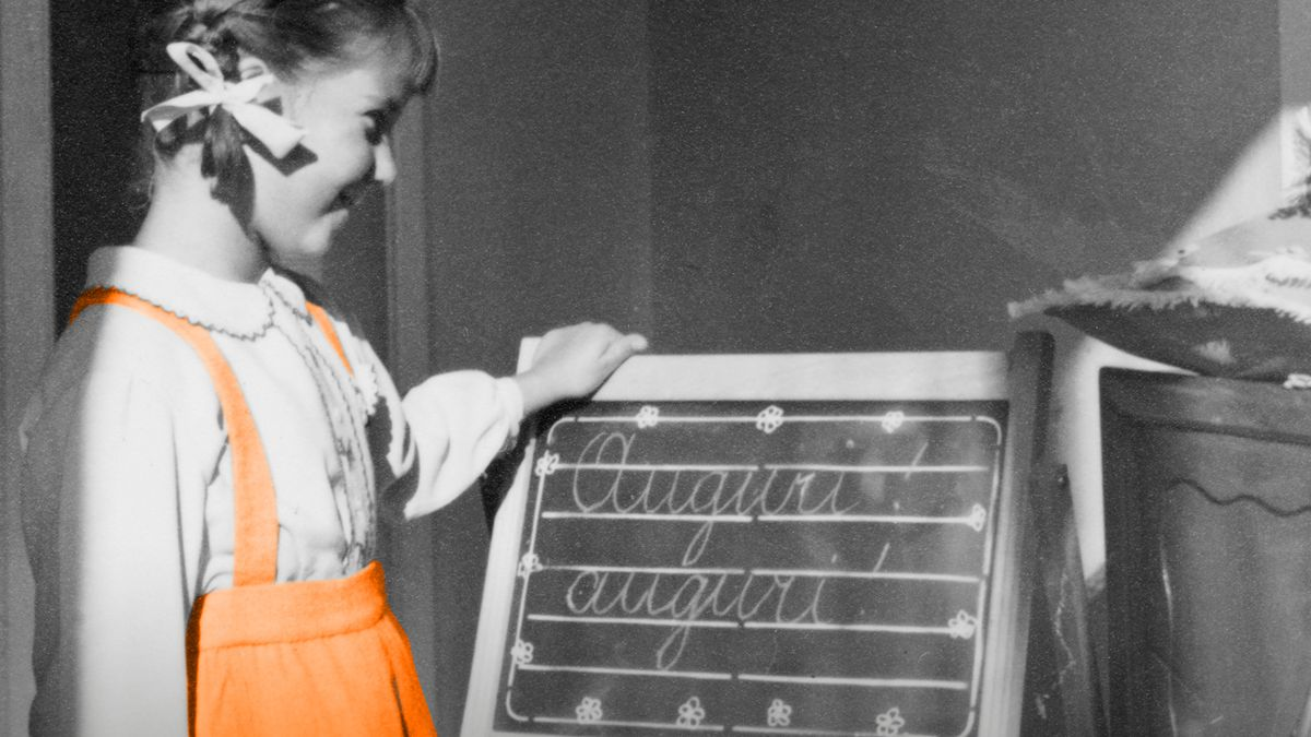 """Schülerin vor einer Tafel, auf der """"auguri, auguri"""" steht"""