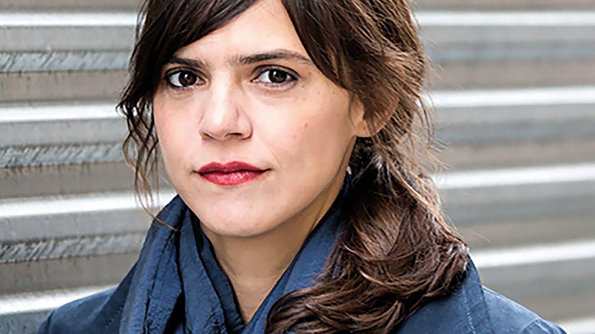 Autorin Valeria Luiselli blickt, im Freien auf einer großen Treppe stehend, ernst in die Kamera