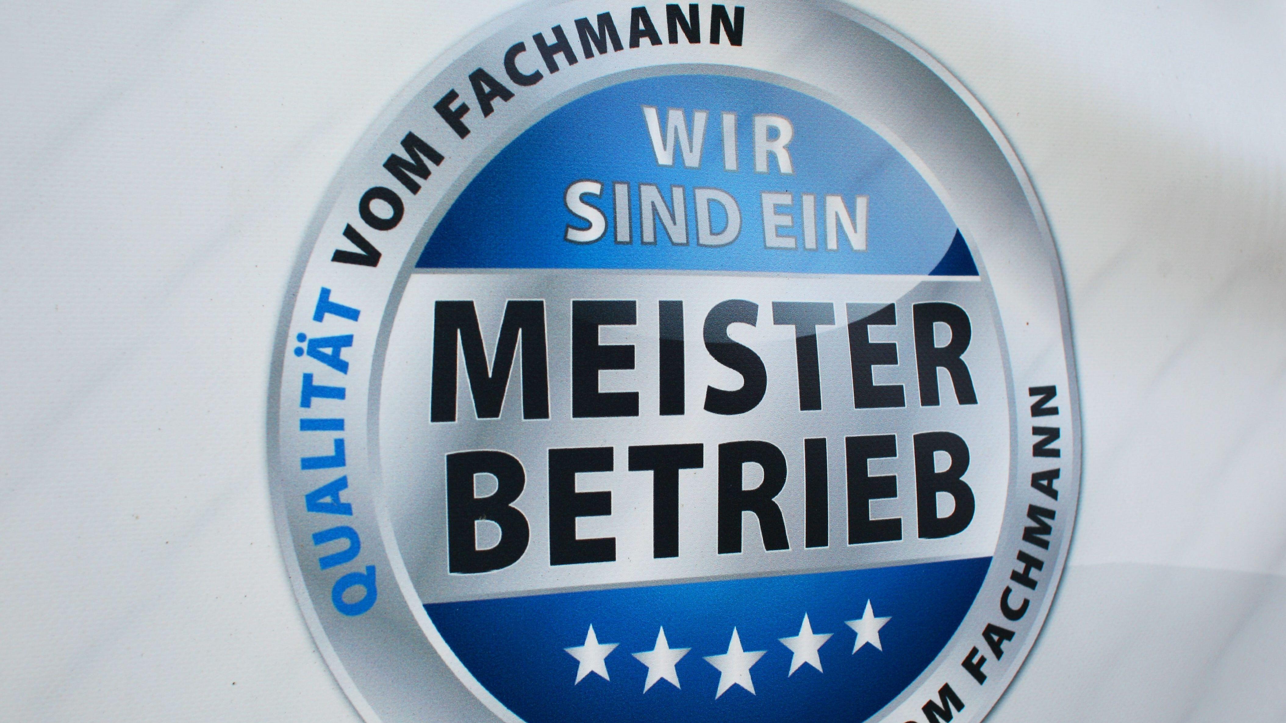 Ein Siegel auf einem Schild weist eine KFZ-Werkstatt als Meisterwerkstatt aus