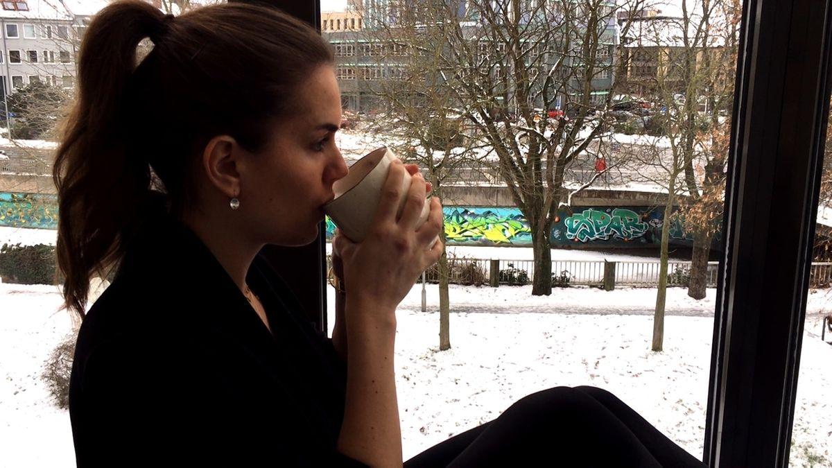 Eine Frau trinkt aus einem Becher.