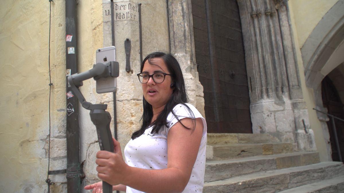 Eine Frau hält einen Selfie-Stick mit Handy vors Gesicht