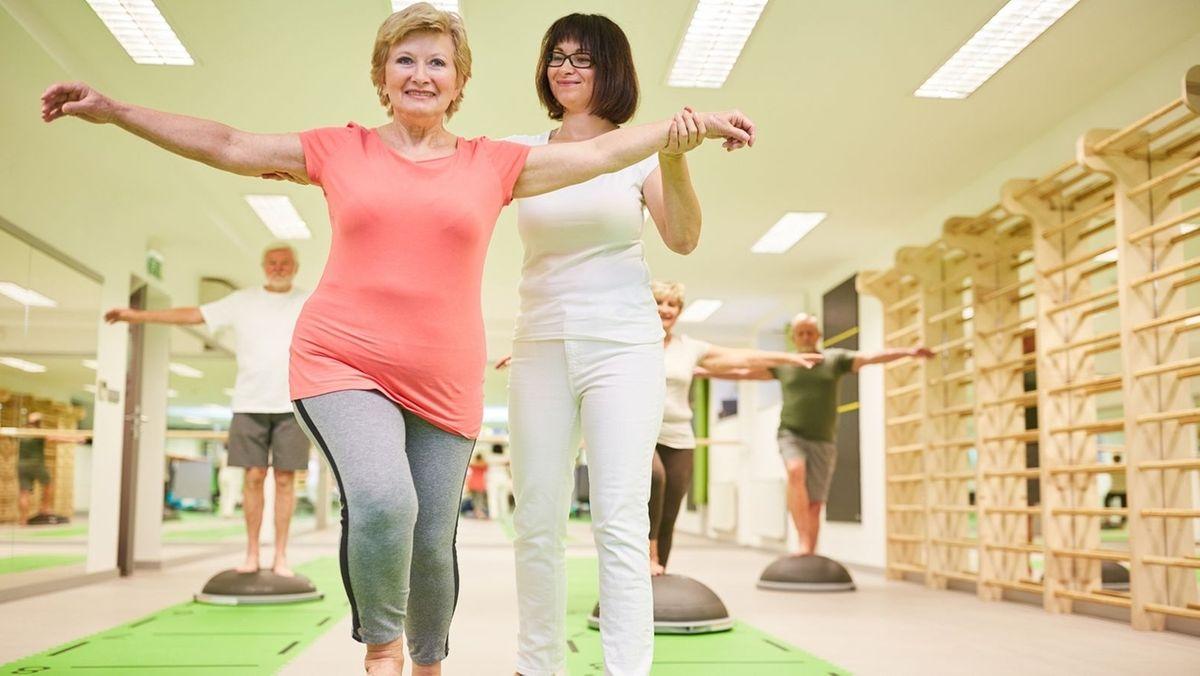 Eine Therapeutin greift einer Reha-Patientin bei ihren Bewegungsübungen unter die Arme.
