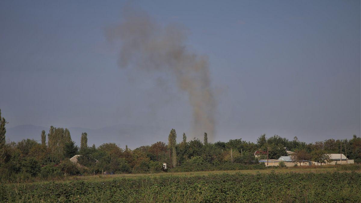 Feld und Bäume, eine kleine Häusergruppe, dahinter steigt eine Rauchsäule auf.