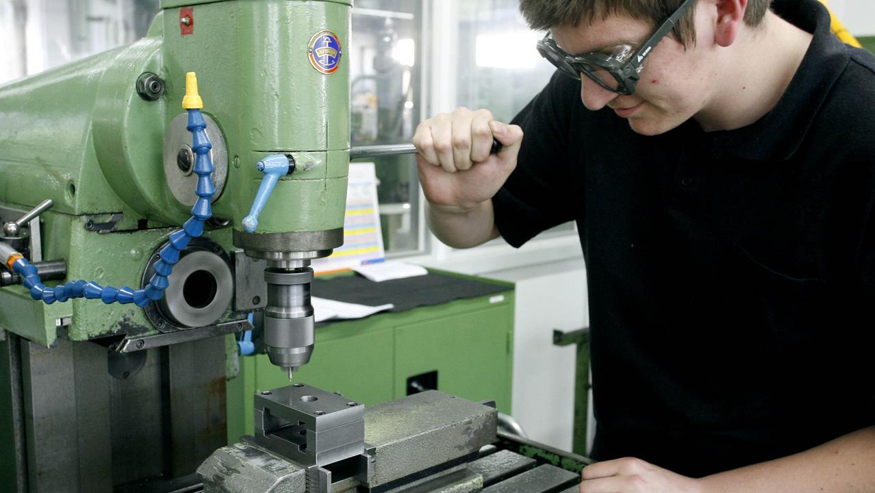 Azubi an Maschine eines Kabelherstellers
