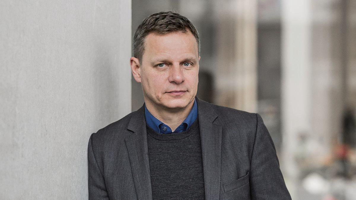 Der Schriftsteller und Jurist Georg M. Oswald in Jacket mit dunklem Pulli drunter blickt den Betrachter direkt an.