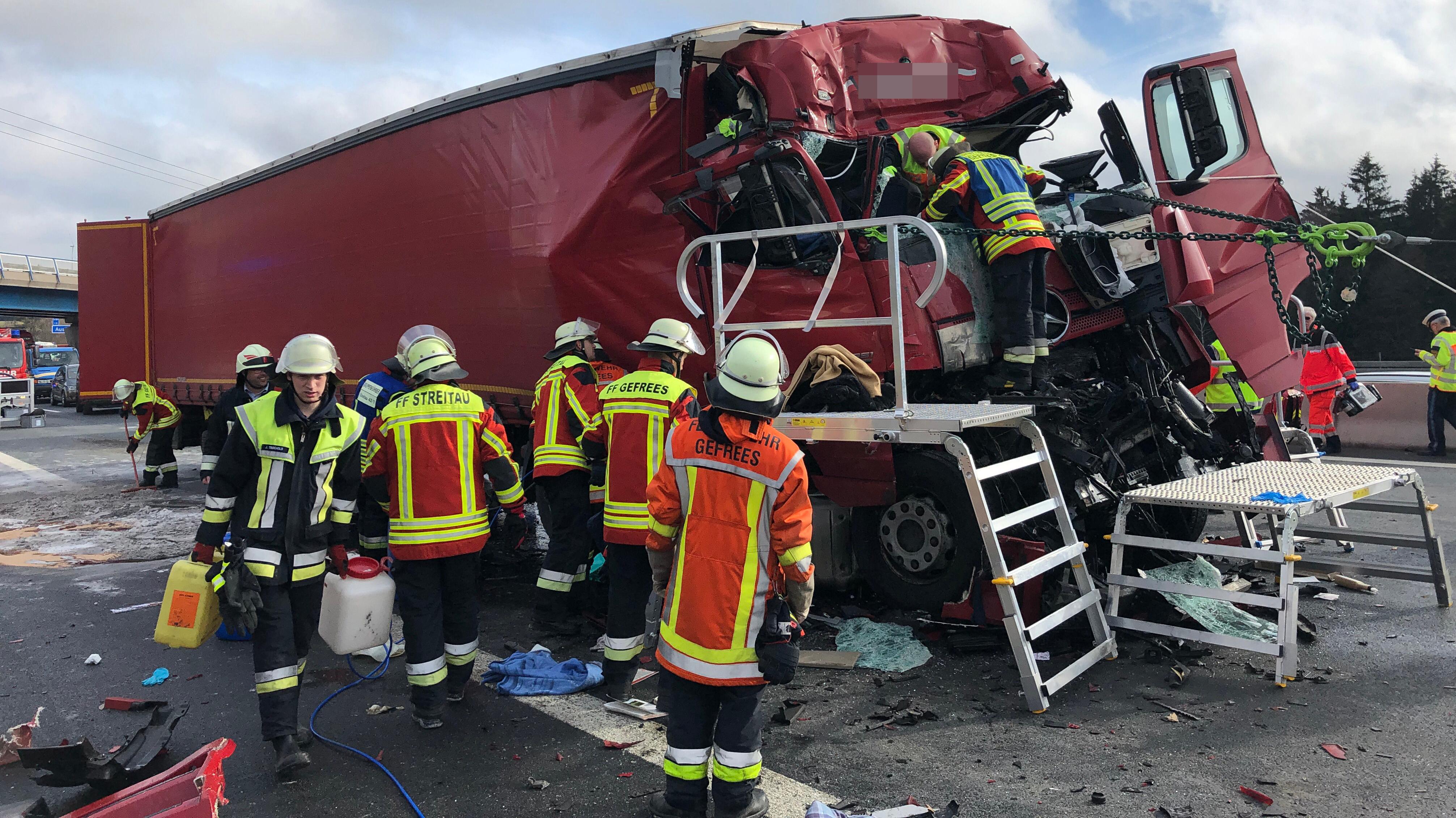 Ein völlig demolierter Lkw steht auf einer Autobahn, daneben stehen Einsatzkräfte.