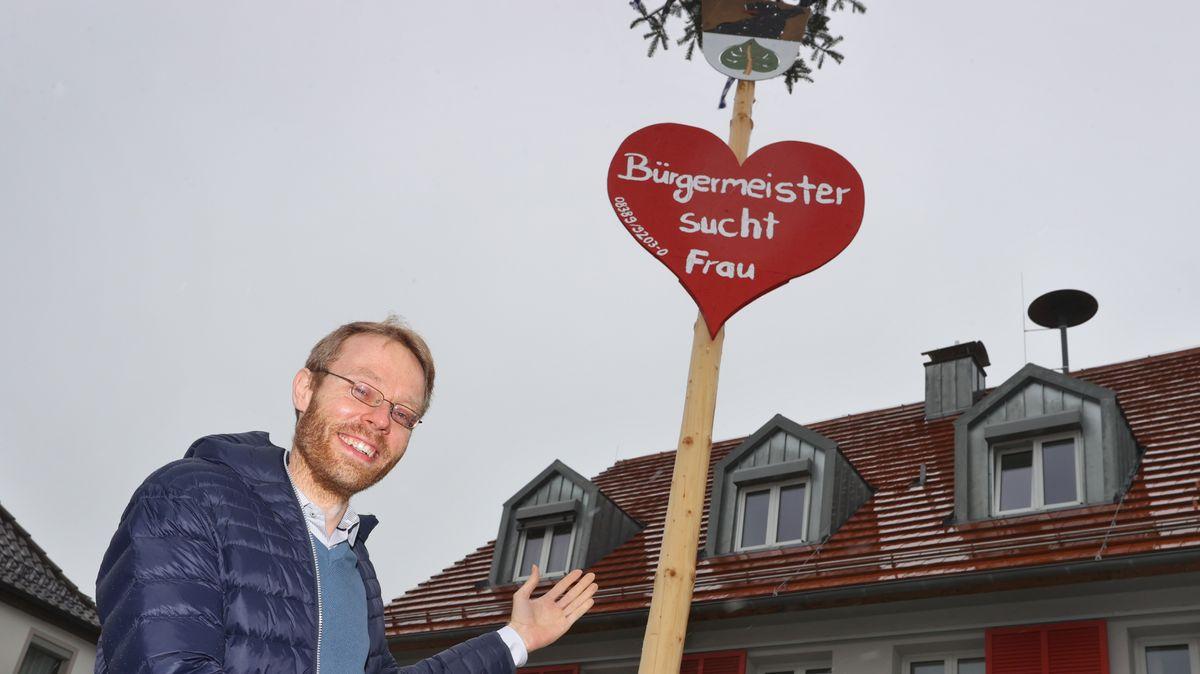 """Bürgermeister Jörg Aghte vor seinem Rathaus. Im Hintergrund ist ein Herz mit der Aufschrift """"Bürgermeister sucht Frau"""" an einem Maibaum befestigt"""