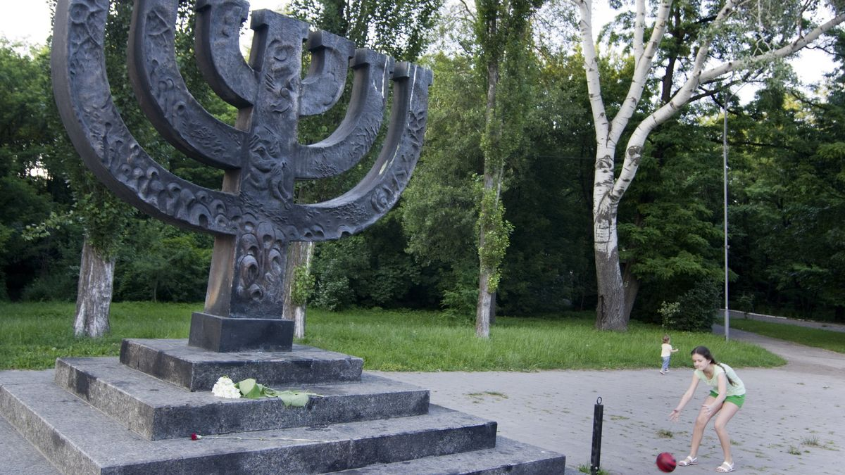 Menora-Leuchter in Stein an der Gedenkstätte Babi Yar, ein Mädchen spielt daneben, es läuft einem roten Ball hinterher