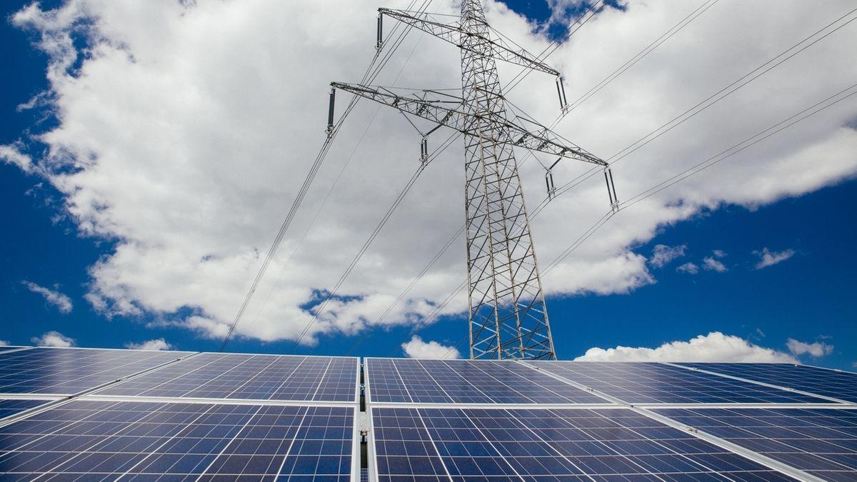 Solarzellen vor Hochspanungsmast