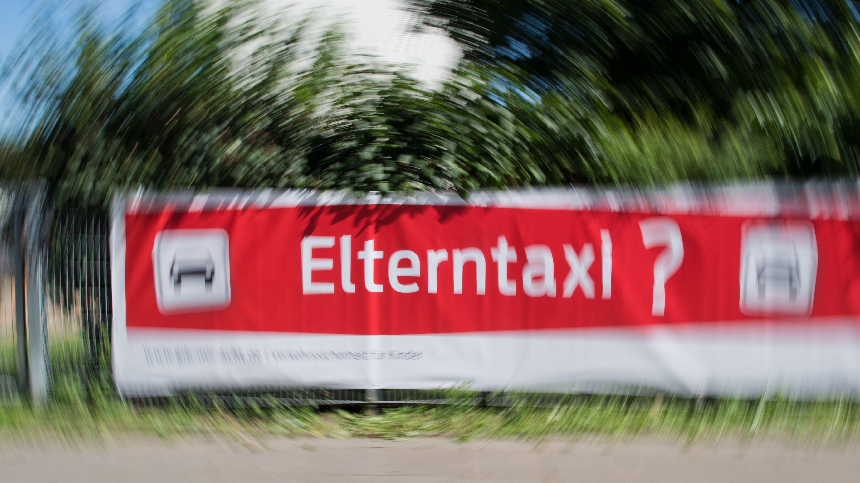 """Ein Schild mit der Aufschrift """"Elterntaxi?"""""""