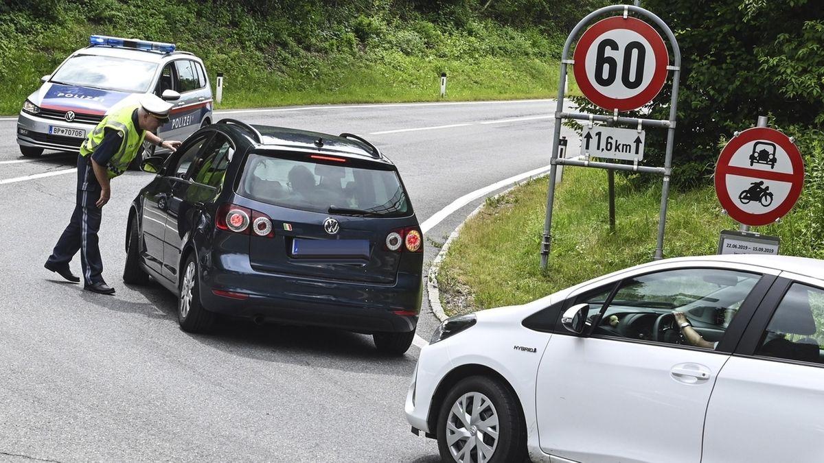 Österreich, Innsbruck: Ein Polizist hält Autos auf einer Straße an.