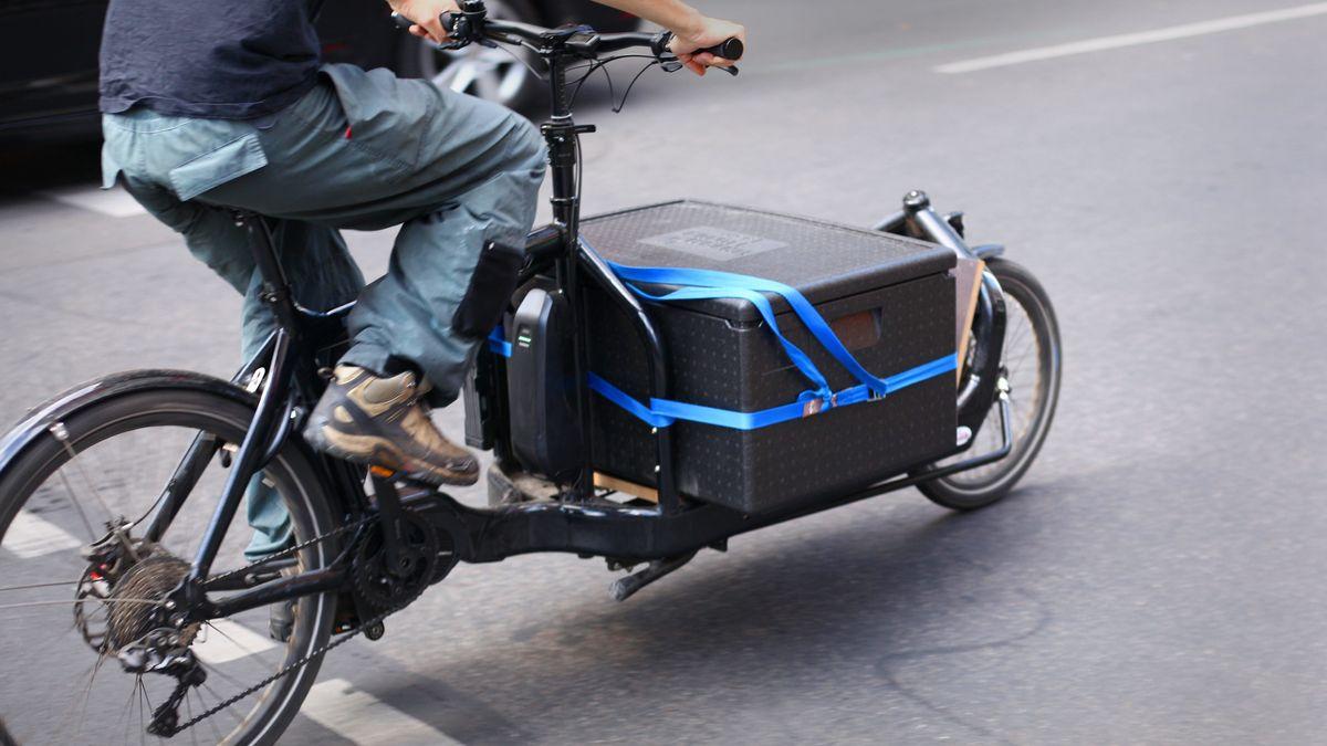 Ein Mann fährt mit einem Lastenfahrrad mit E-Antrieb über eine Straße