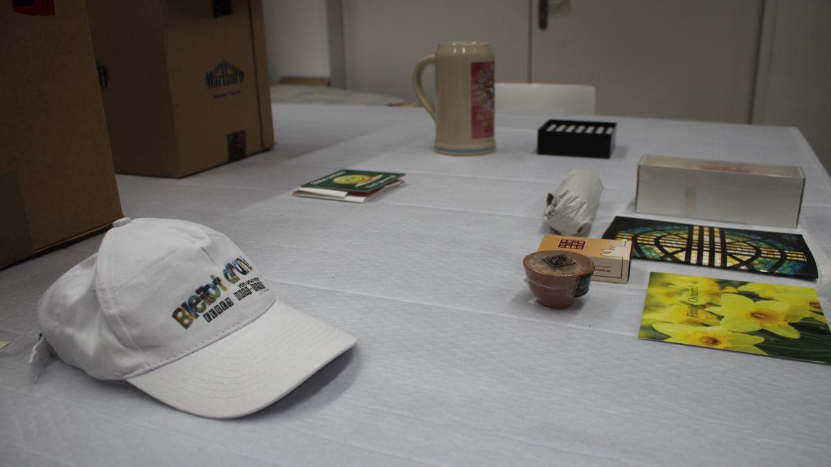 Ein Käppi, ein Tonkrug und diverse kleinere Gegenstände liegen ausgebreitet auf einem Tisch.