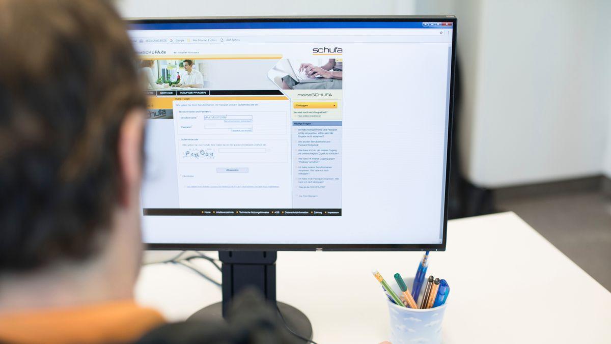 Ein Mann loggt sich am Computer auf der Schufa-Website ein.