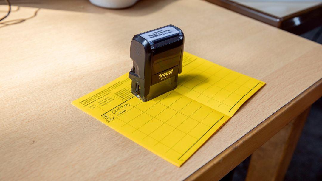 Ein fertig ausgefüllter Impfausweis liegt bei einer mobilen Impfstation auf einem Tisch.
