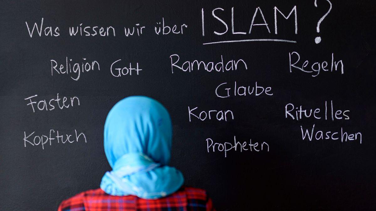 Eine muslimische Schülerin vor einer Tafel mit Begriffen aus dem Islam im Islamunterricht.