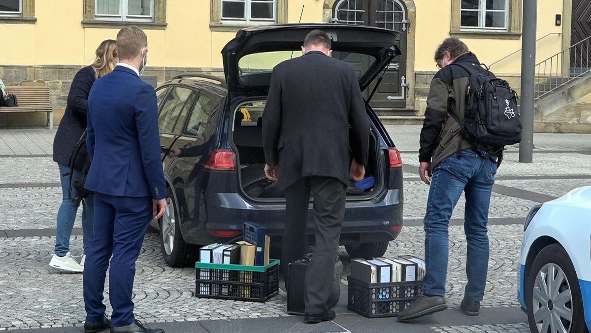 Vier Personen stehen am Heck eines Autos, der Kofferraum ist geöffnet, auf dem Boden stehen mit Ordnern gefüllte Kisten.