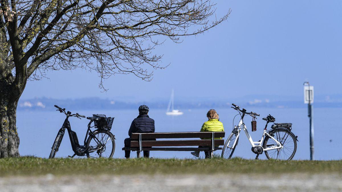 Zwei Menschen sitzen auf einer Parkbank