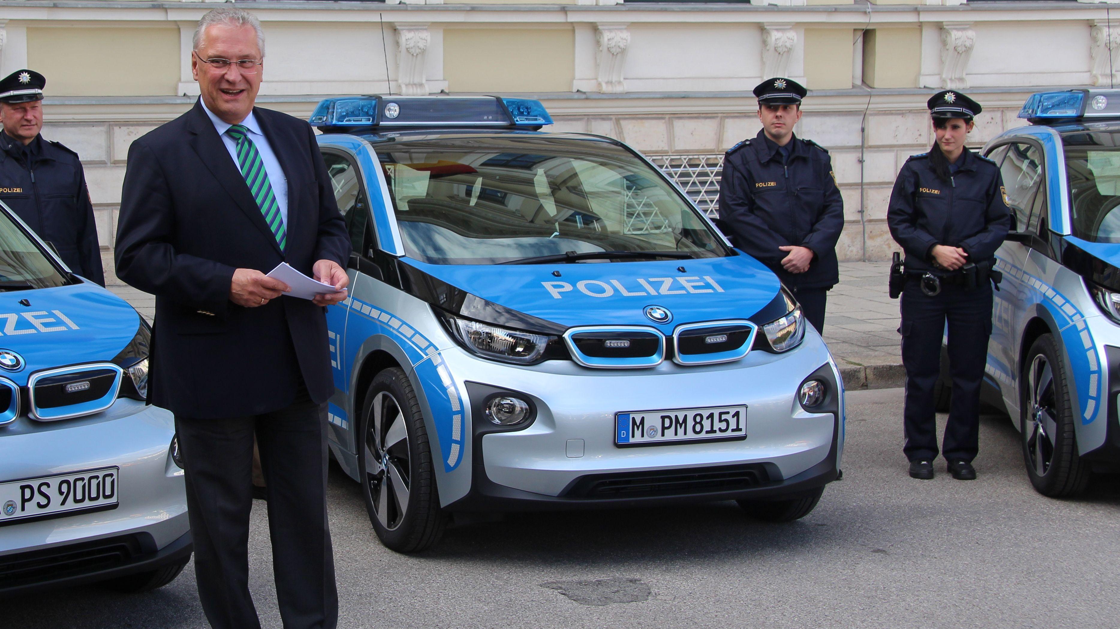 Archivbild: Innenminister Herrmann posiert vor den Elektrodienstwagen der Polizei