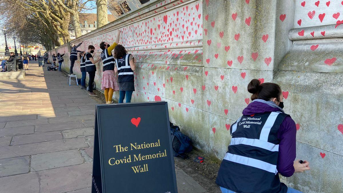 Angehörige von Corona-Opfer bemalen in London eine Betonwand mit Herzen.
