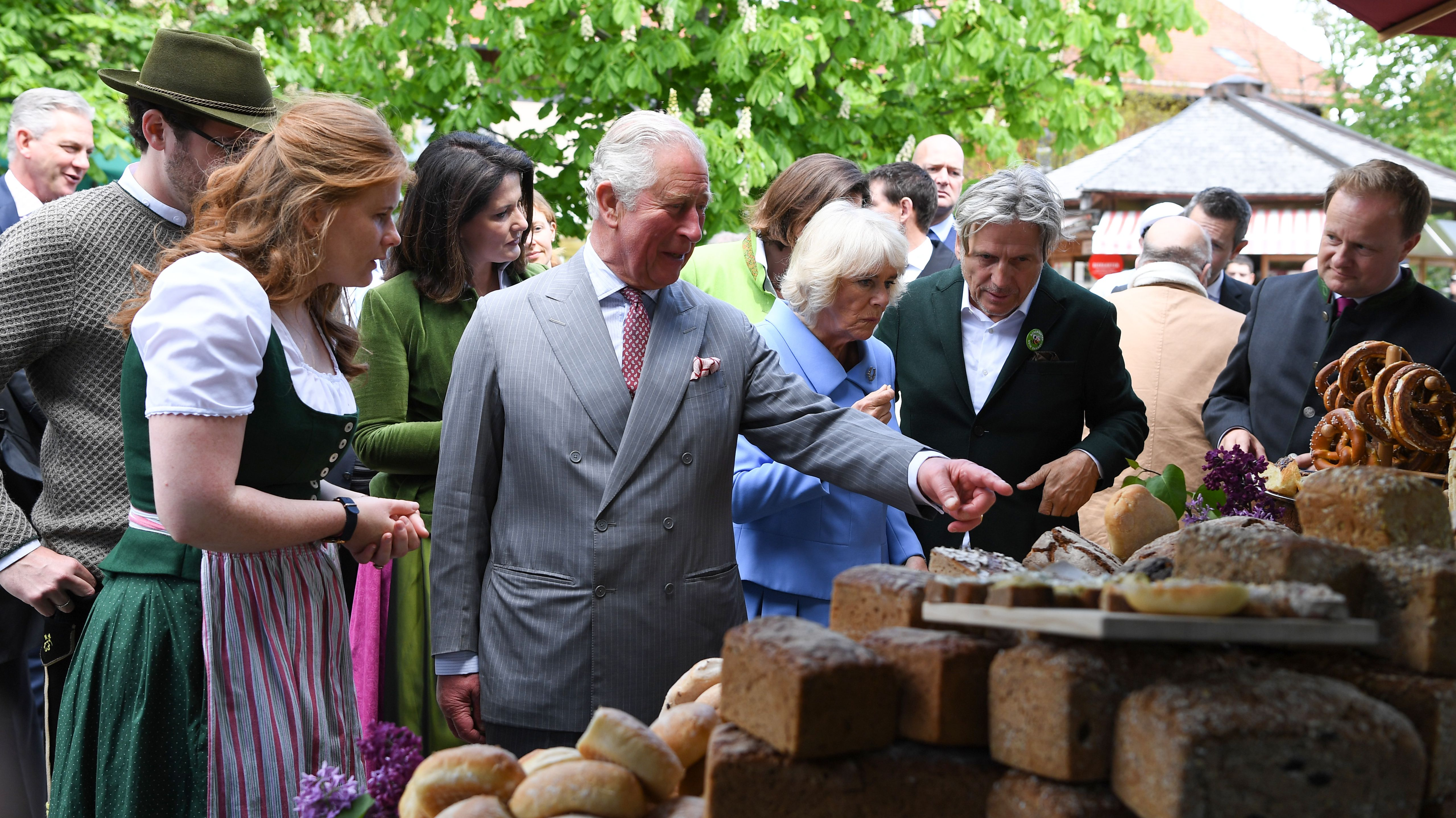 """Prinz Charles und Herzogin Camilla lassen sich auf dem Bio-Hof """"Herrmannsdorfer Landwerkstätten"""" verschiedene Brotsorten zeigen."""