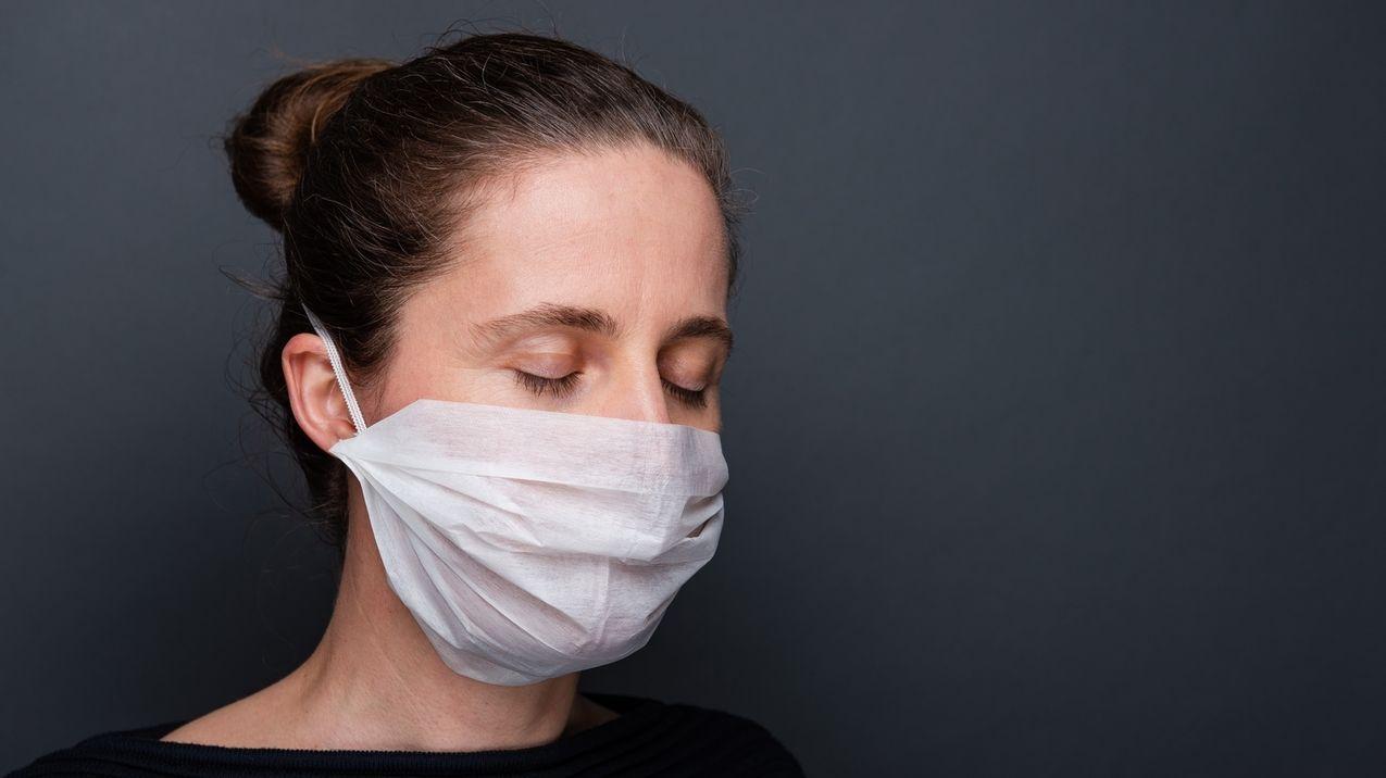 Eine Frau mit geschlossenen Augen trägt eine Hygienemaske.