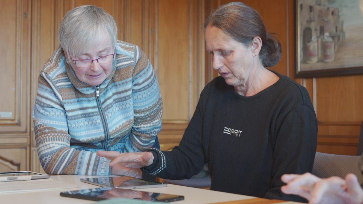 Betreuerin und Demenzpatientin betrachten Tablet-PC