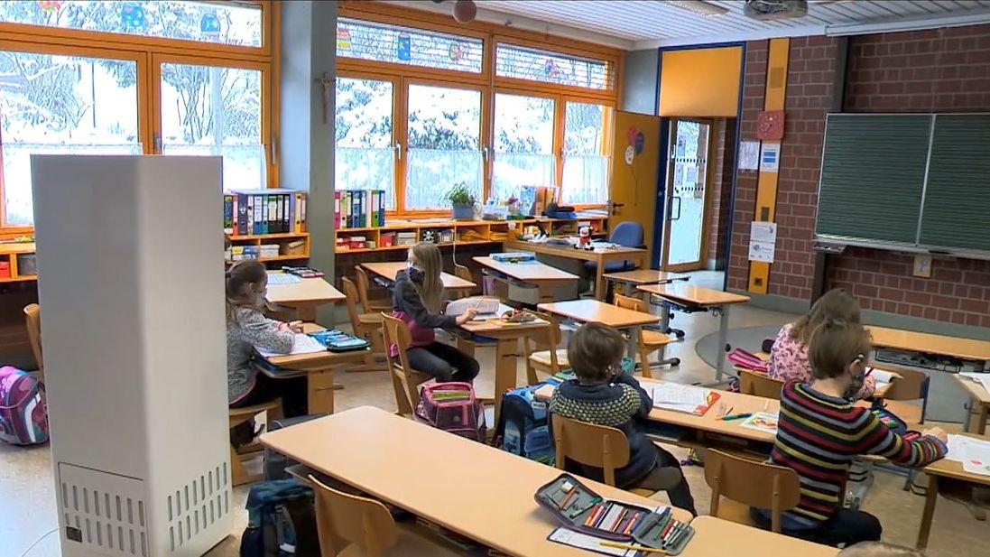 Mehrere Kinder sitzen in einem Klassenzimmer, links steht ein hoher Kasten - ein Gerät zur Luftfilterung.