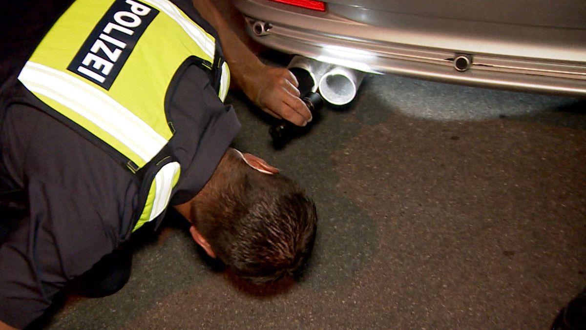 """Ein Beamter der """"Kontrollgruppe Poser- und Tuningszene"""" kontrolliert einen Wagen"""