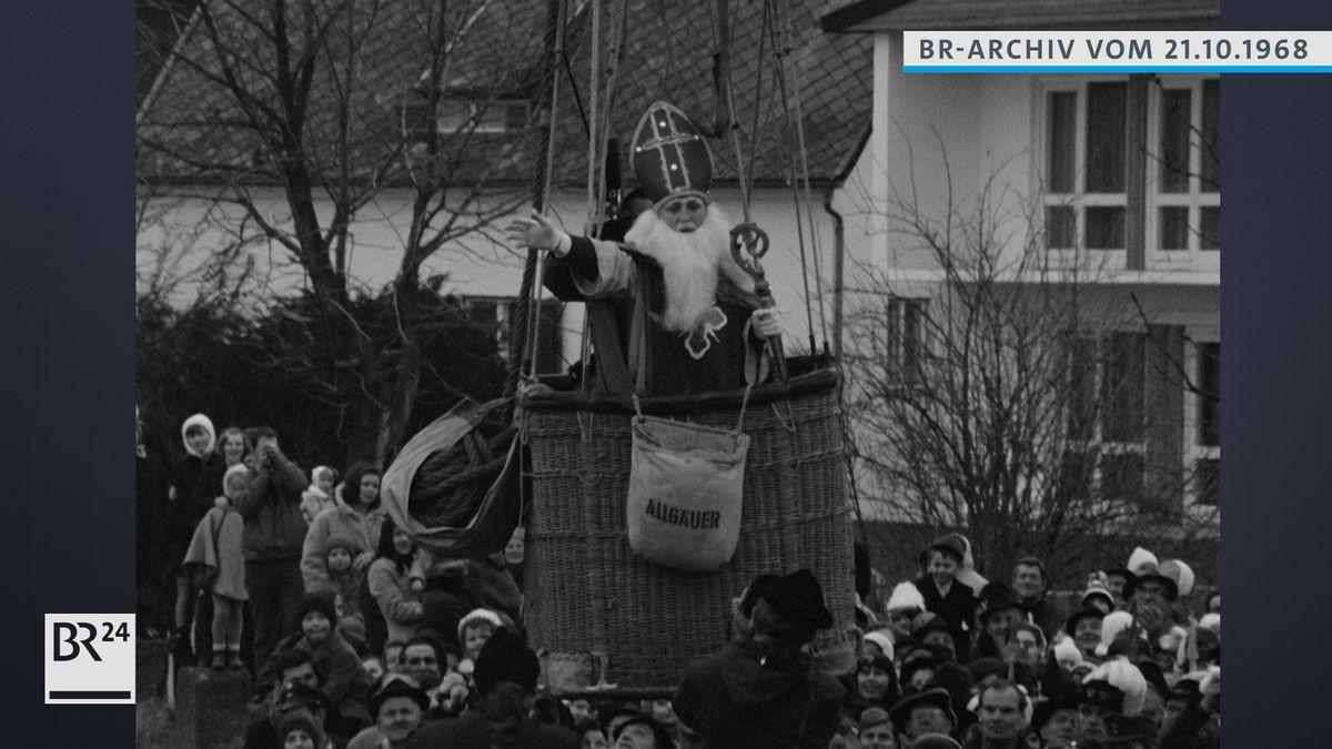 Nikolaus im Heißluftballon, den Menschen zuwinkend