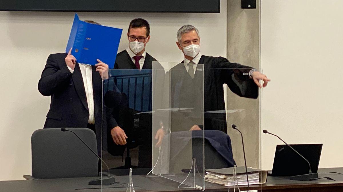 Der Angeklagte im schwarzen Anzug verdeckt sein Gesicht mit einem blauen Ordner, daneben seine beiden Verteidiger.