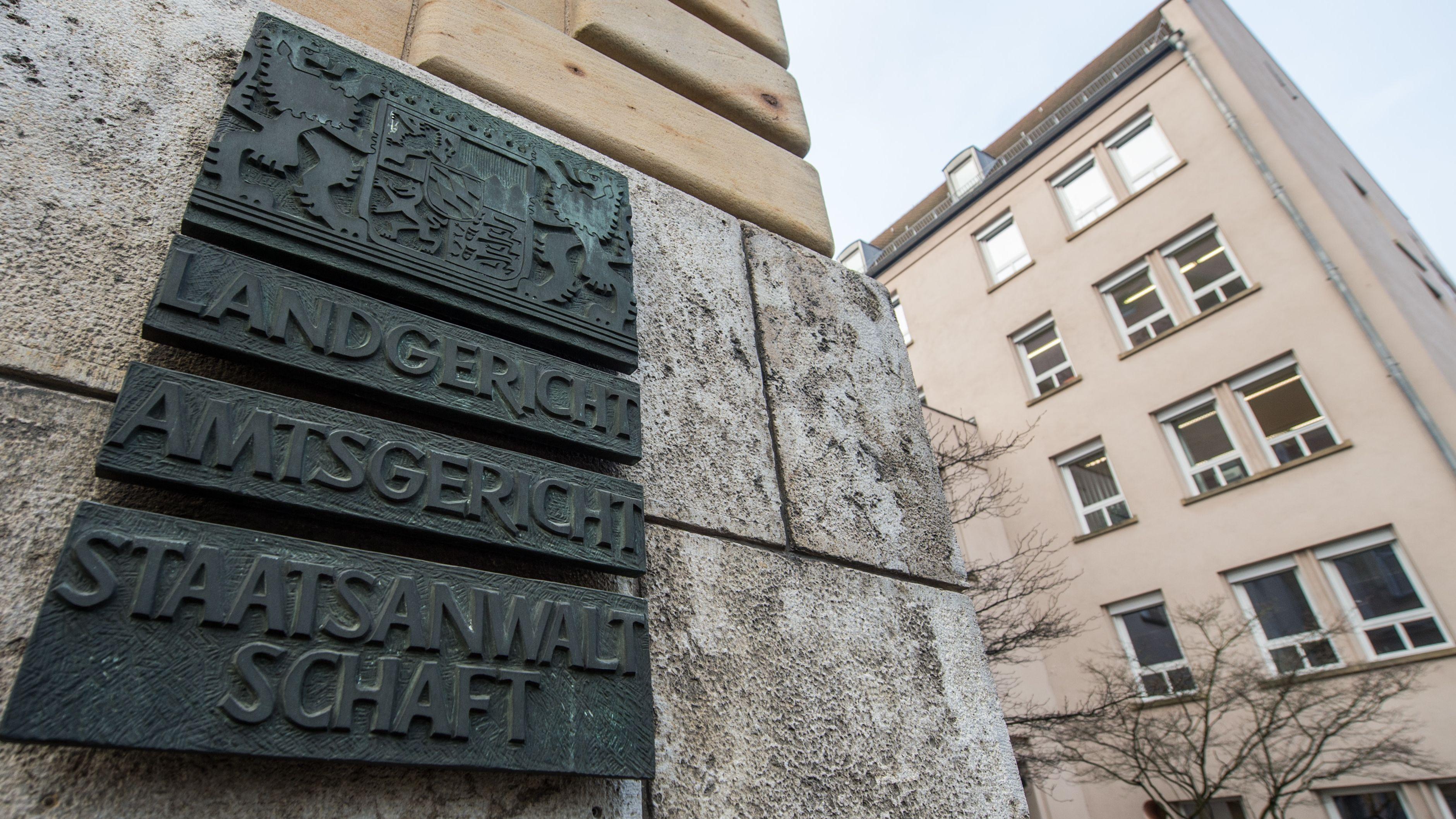 """Ein Schild mit der Aufschrift """"Landgericht, Amtsgericht, Staatsanwaltschaft"""" an der Aussenwand des Gebäudes."""
