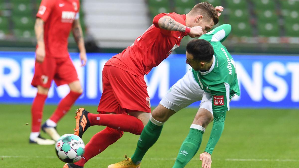 Bremens Kevin Möhwald (r) kämpft gegen Augsburgs Andre Hahn um den Ball.