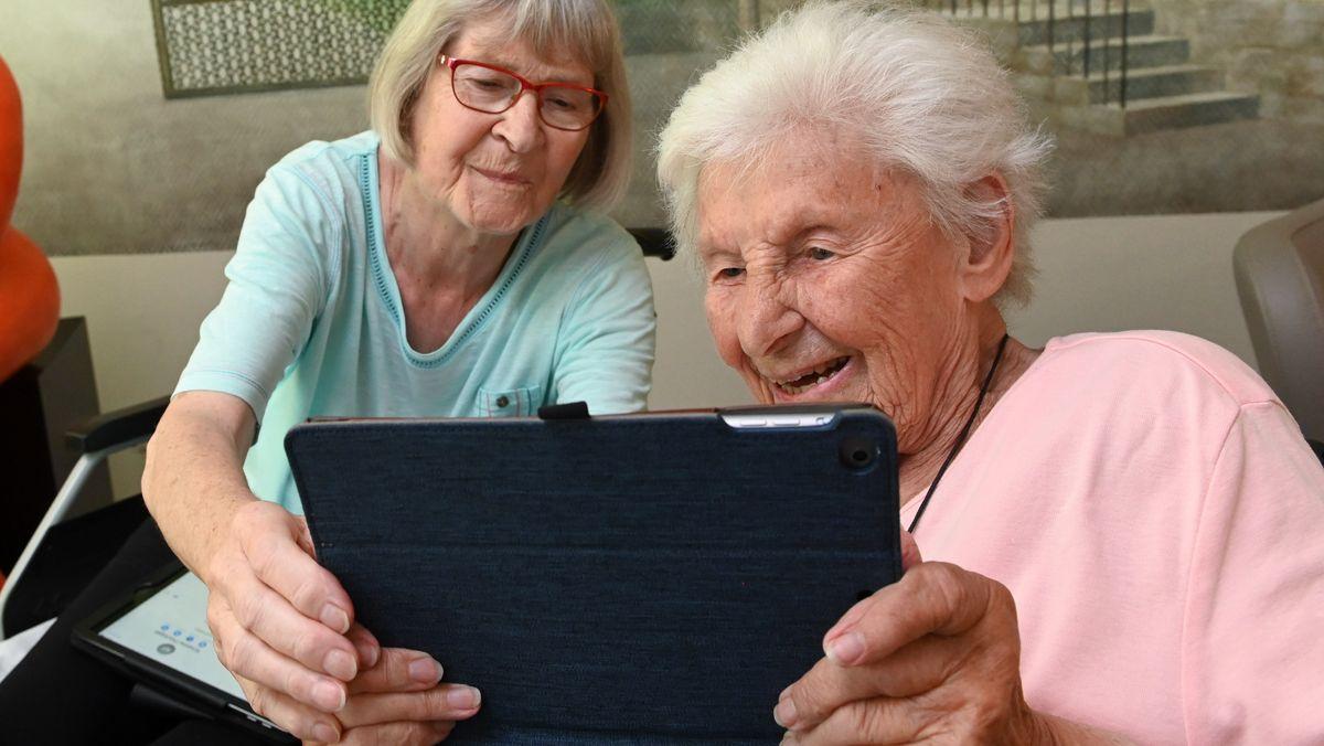 Zwei alte Frauen schauen auf ein Tablet und freuen sich.