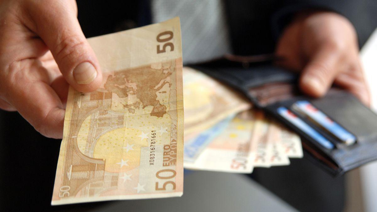 Ein Mann holt einen 50-Euro-Schein aus seinem Geldbeutel