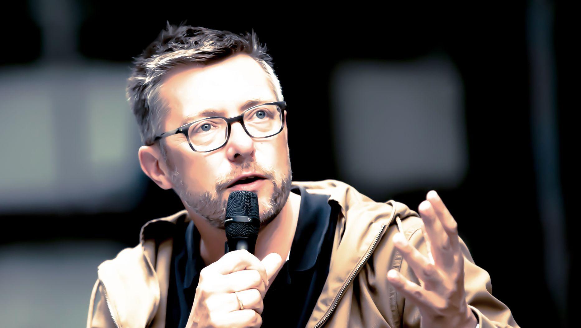 Mann mit Brille und hellbrauner Jacke gestikuliert mit Mikrofon