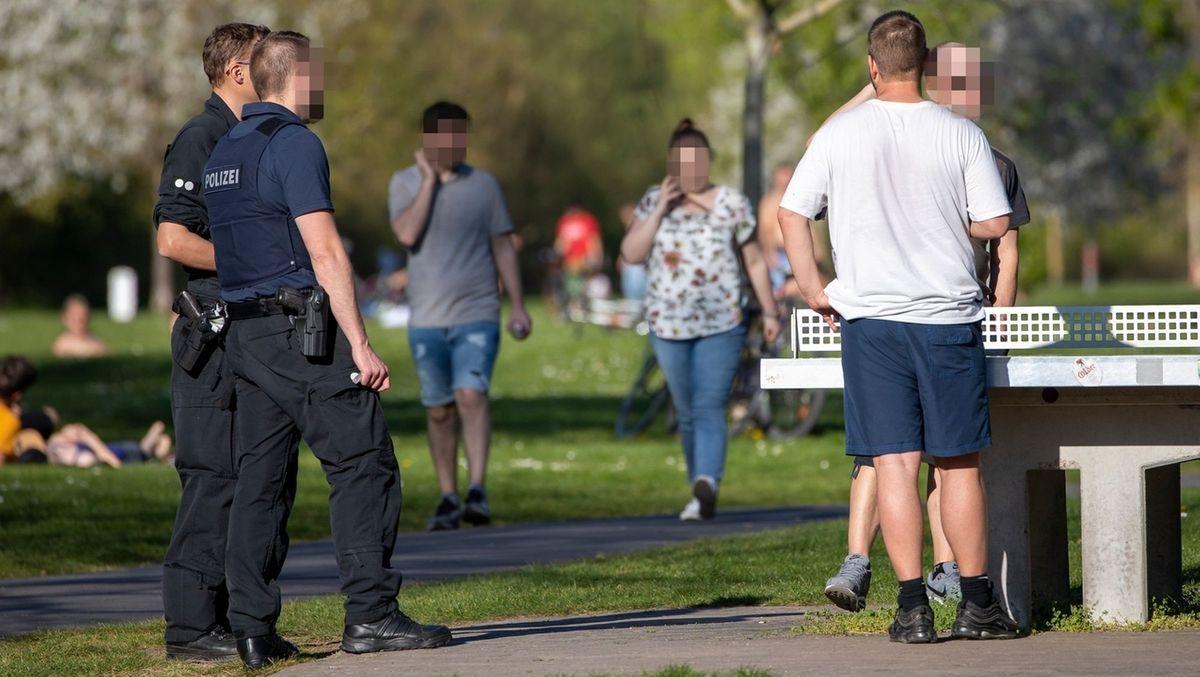 Zwei Polizisten kontrollieren zwei Männer an einer Tischtennisplatte