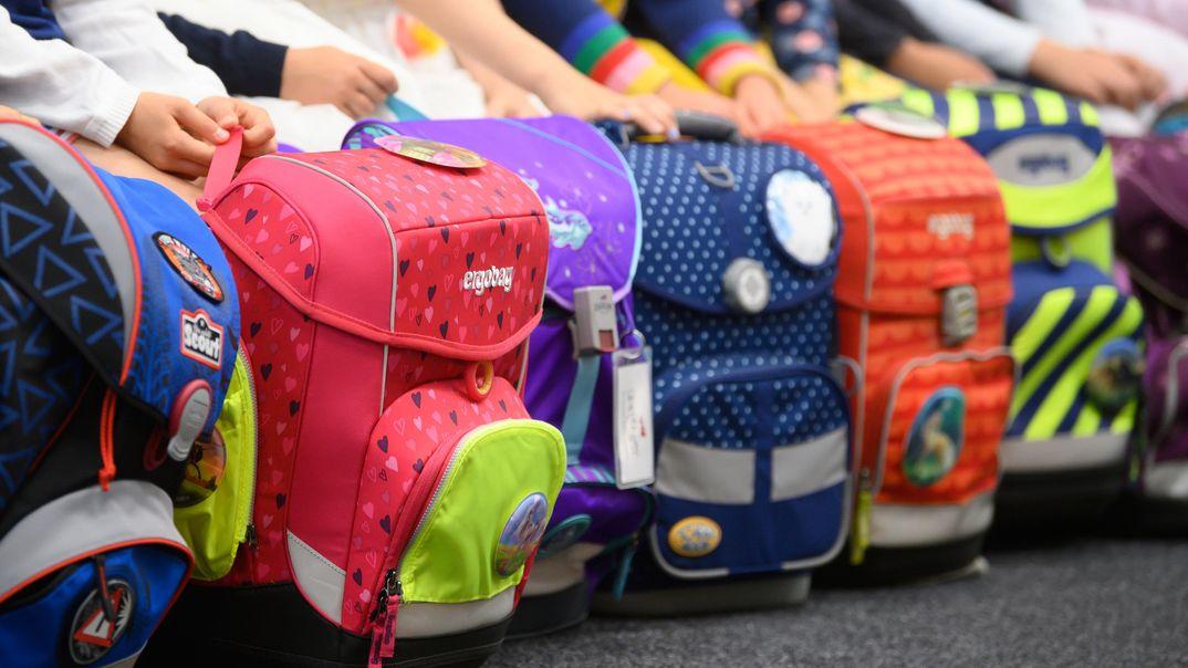 Schultaschen stehen zum Schulanfang in einer Reihe.