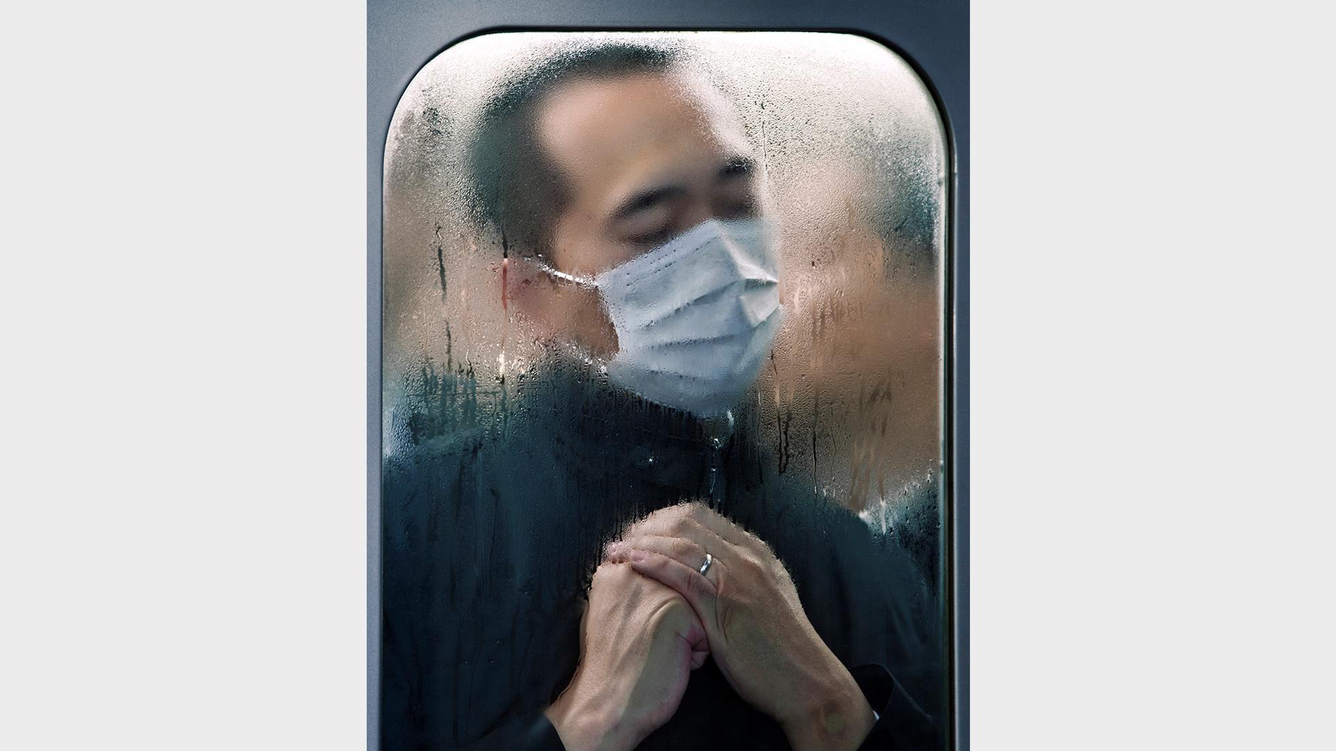 Ein junger Chinese hinter einer beschlagenen Scheibe im Zug in Tokyo. Er trägt eine Atemschutzmaske. Die Augen sind friedlich geschlossen, er hält seine rechte Faust in der linken Hand wie zum Gebet.
