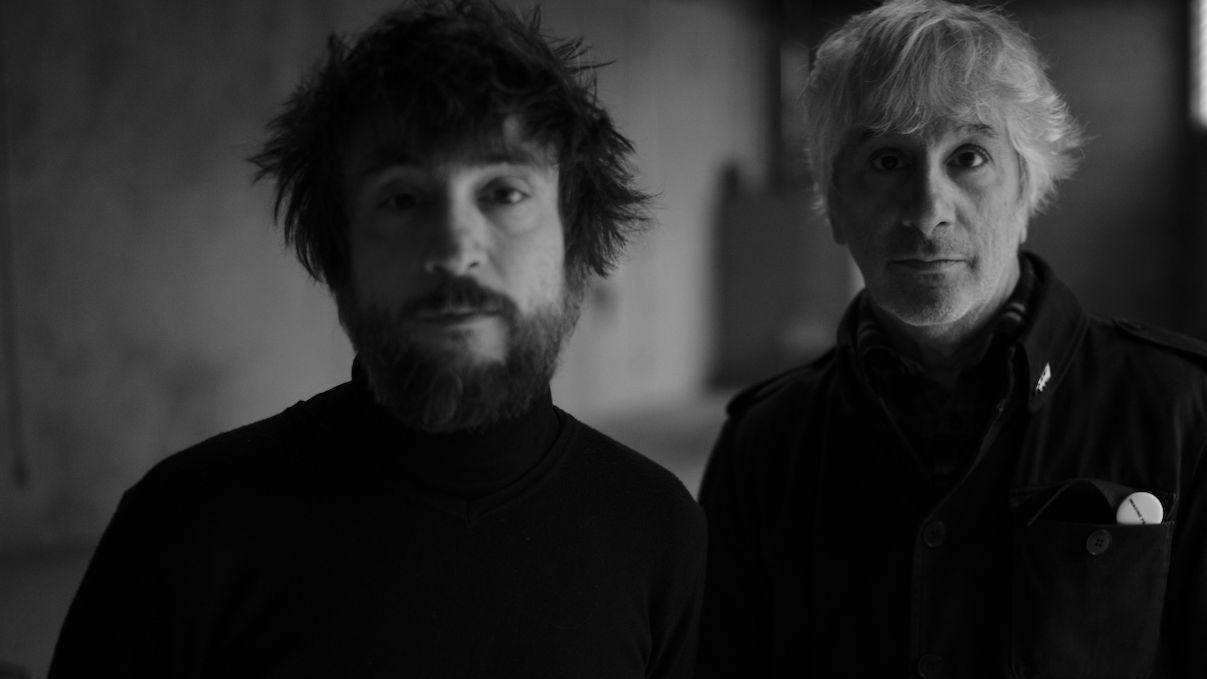Lee Ranaldo und Raül Refree blicken, nebeneinander stehend, ernst in die Kamera (Schwarzweißfotografie)