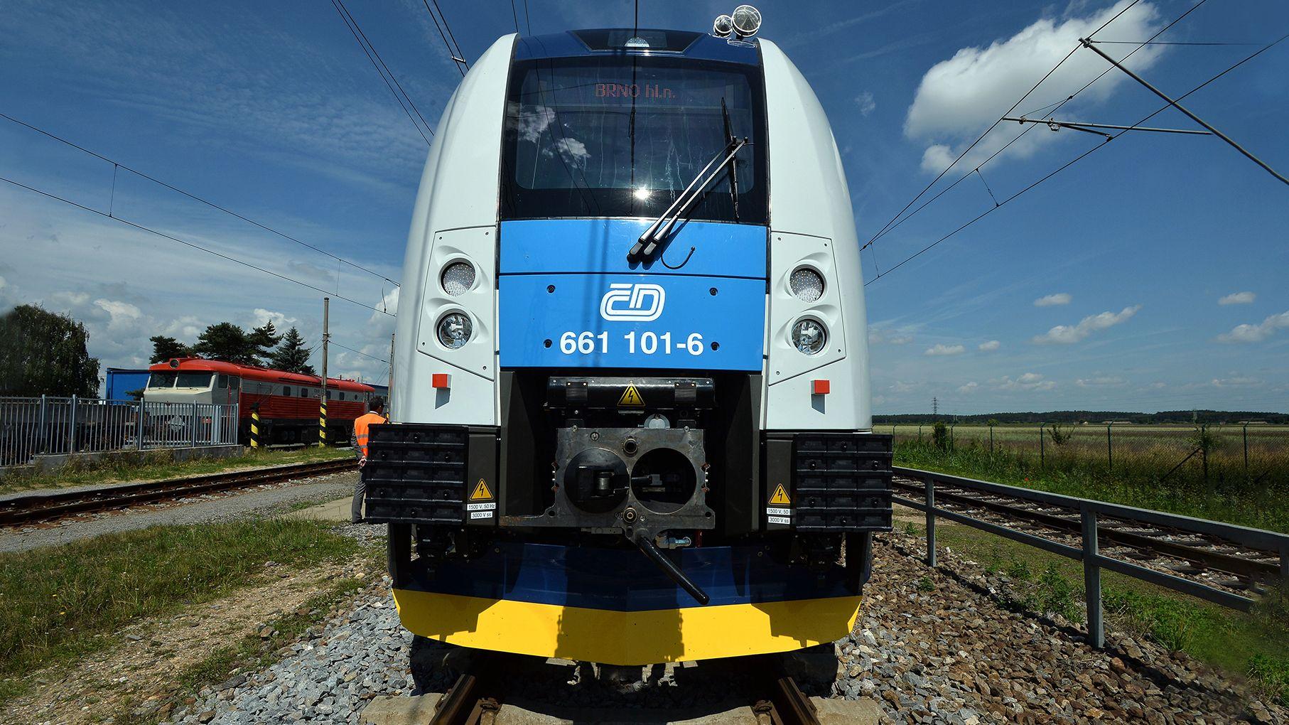 Ein blau-grau-gelber Zug aus Tschechien steht auf einem Gleis an einem Bahnhof, im Hintergrund ist eine unbebaute Landschaft zu sehen.