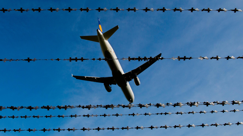 Flugzeug fliegt über Stacheldrahtzaun