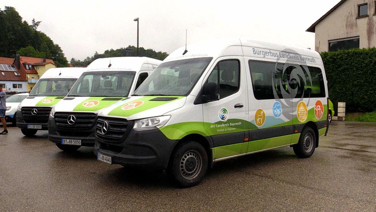 Drei weiß-grüne Bürgerbusse stehen auf einem Parkplatz.