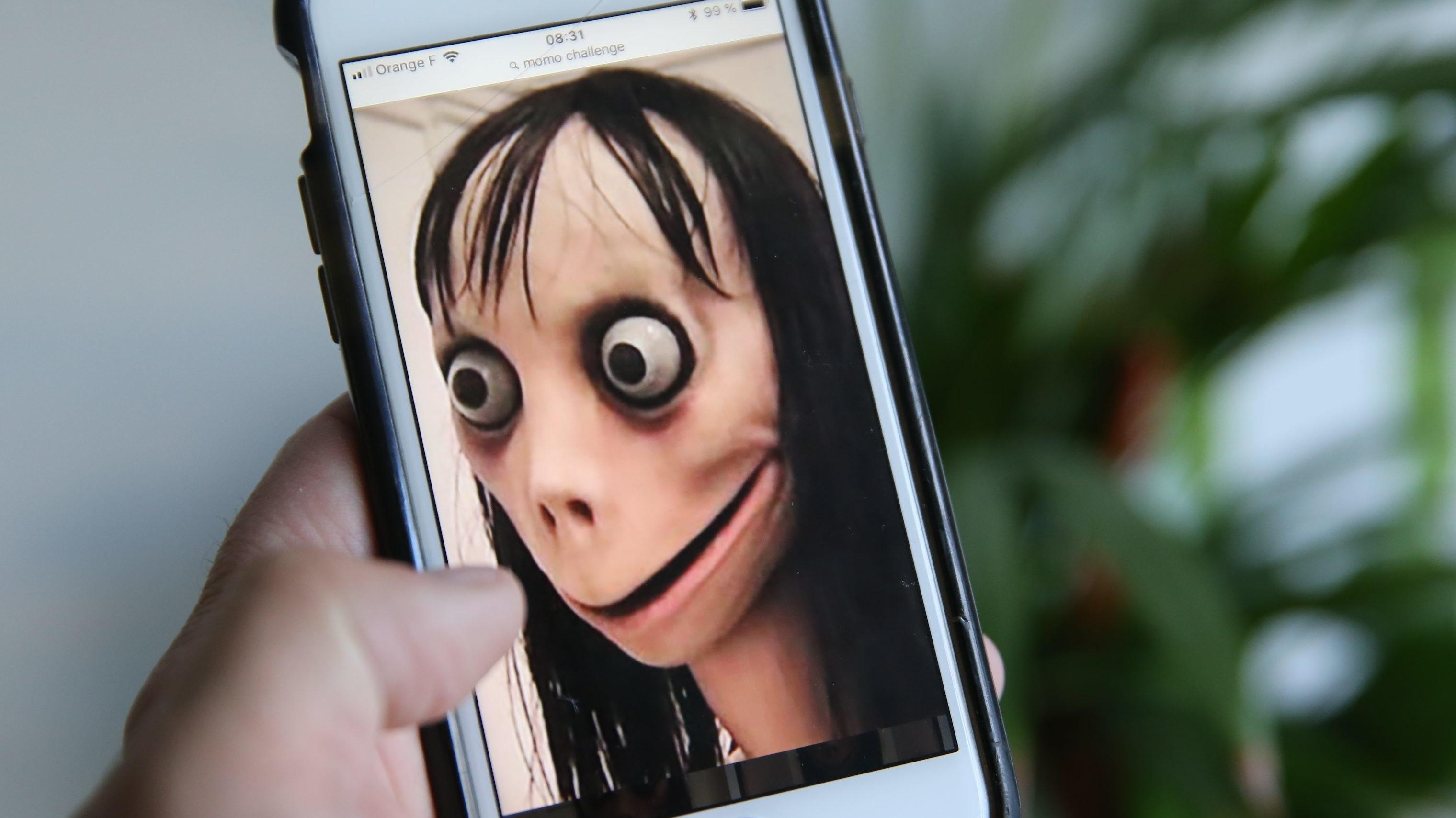 """Horrorfigur """"Momo"""" auf einem Smartphone"""