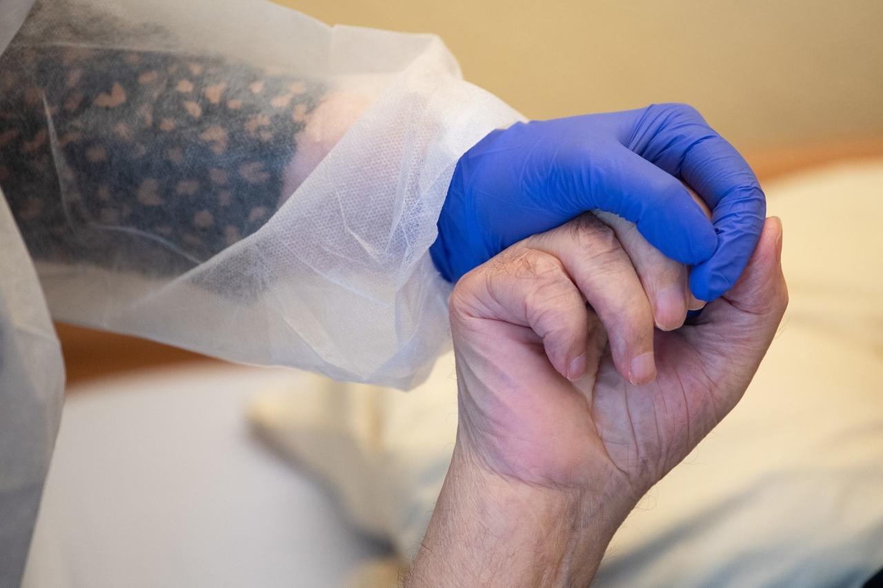 Tübingen: Eine Altenpflegerin in Schutzkleidung hält die Hand eines Bewohners.