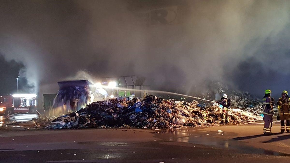 Abgelöschte Abfallhaufen vor der Halle auf dem Recyclinghof